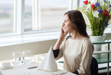 happy woman calling on smart phone at restaurant