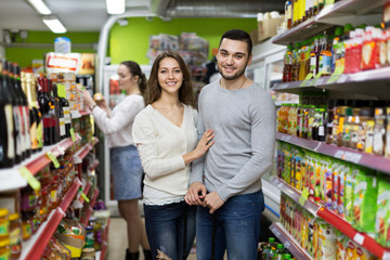 Customers at beverages section of supermarket