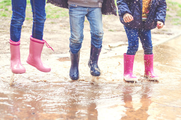 Low section of three children in wellington boots jumping in a puddle