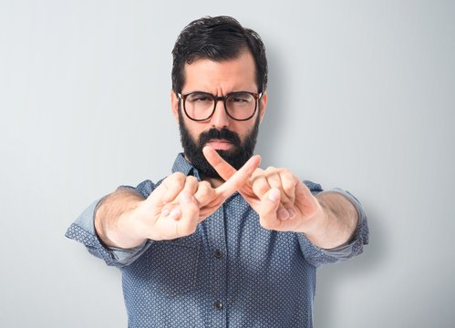 Young hipster man doing NO gesture