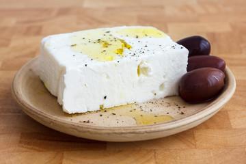 Greek feta cheese, oil, kalamata olives on rustic plate board.