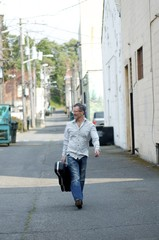 Man With Guitar Case Walking Down Alley, Port Angeles, Washington, USA