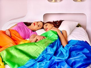 Lesbian women at erotic foreplay game in bed.