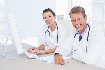 Smiling female and male doctors looking at camera