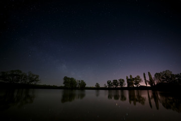 Smooth surface of forest lake on a background of the night sky a
