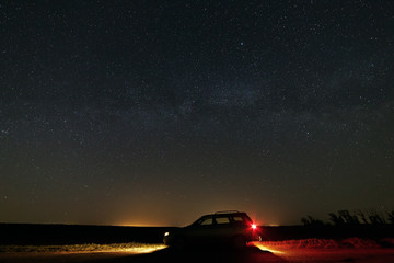 The car with the headlights switched on the background of the Mi