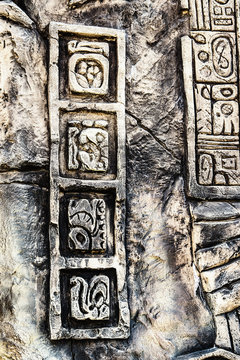 Ancient Mayan hieroglyphics in stone, from the ruins