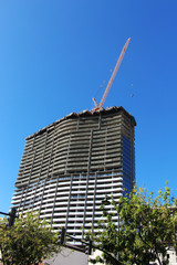 Crane and high-rise building under construction against blue sky