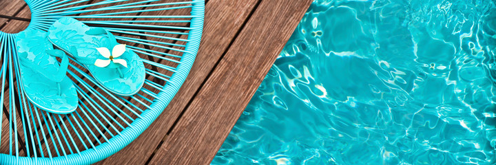 Turquoise blue garden chair and flip flops on on the edge of a swimming pool, panoramic view