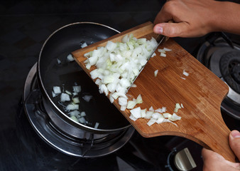 Hands drop chopped onions from board into pan