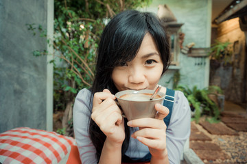 Beautiful resting asian woman with cup of coffee