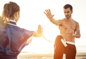 couple training martial arts on the beach