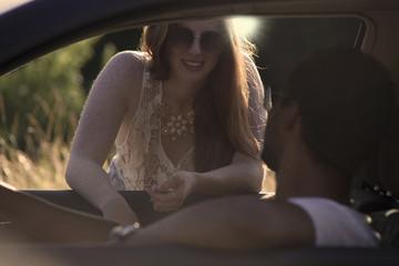 Sexy redhead woman talking to a man in a car