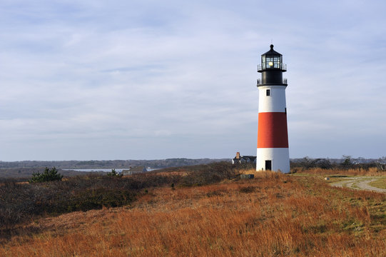 Sankaty Head Lighthouse Nantucket Cape Cod Massachusetts in the autumn with fall colors. It is a red and white striped light house on a bluff overlooking the sea. Copy space in the blue sky.