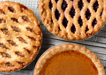 Three pies on cooling racks. High angle closeup shot of fresh baked apple, cherry and pumpkin pies on wire racks on a rustic wood kitchen table. Horizontal format.