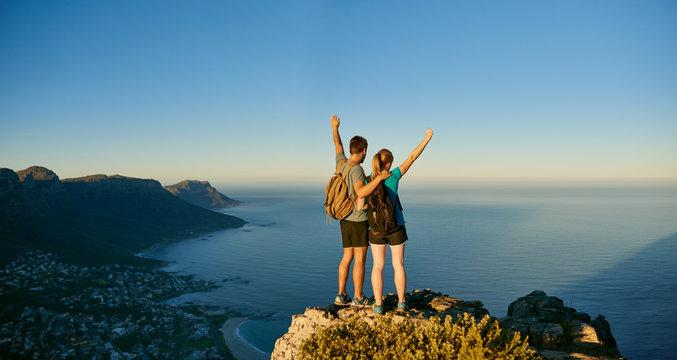 Young couple posing triumphantly on a mountain top