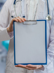 Doctor holds clipboard with empty sheet of paper as frame