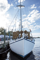 White Sponge Boat Front - White Wooden Sponge Boat with Blue Trim and Drying Sponges Floating in Water at a Dock in Tarpon Springs Florida.