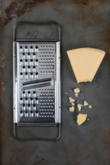 High angle shot of a broken wedge of Parmesan cheese and grater on used baking sheet. Vertical format.