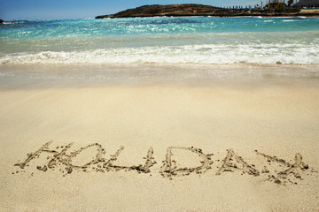 "the word ""holiday"" in the sand on the beach"
