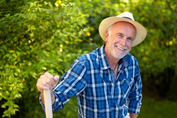 Senior man in garden with straw hat