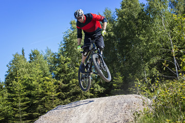 Mountain bike rider jumping kicker