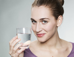 happy young beautiful woman wearing purple shirt displaying glass of pure tap water