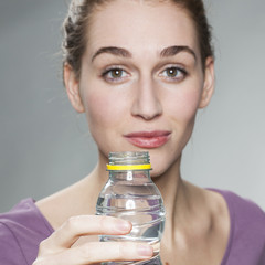 focus on hand holding a bottle of water with a radiant young beautiful woman in background