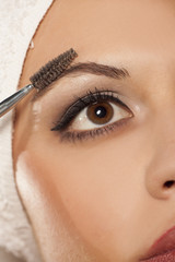 a beautiful young woman comb her eyebrow