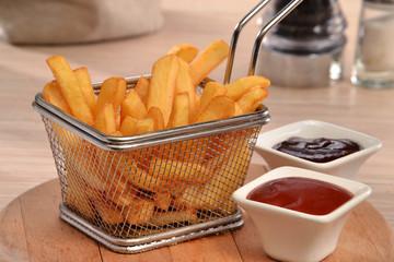 Cesto de patatas fritas y salsas ketchup barbecue..