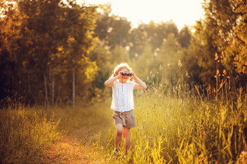 child girl watching birds with binoculars in summer forest
