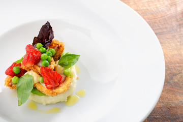 Fine dining, Fried Octopus on potato purree, green peas and fresh strawberries
