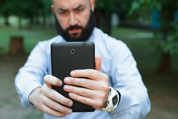 Man with beard taking pictures from tablet computer in summer park