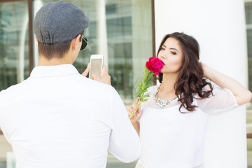 Boy taking photo of his girlfriend on phone camera