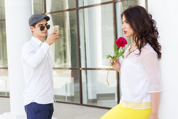 Boy taking photo of his beautiful girlfriend on phone camera