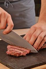 Cortando carne de ternera con un cuchillo,rebanabdo bistec a la Parrilla.