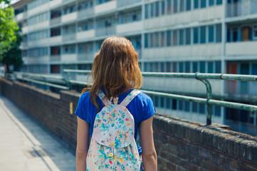 Young woman looking at apartment block