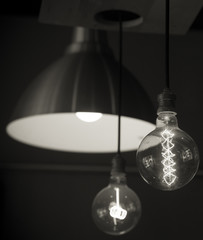Hanged lamps  focused on light bulb black and white