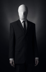 Internet meme and terrible character Halloween theme: very tall burly man with long arms in a suit with bandaged face fabric, an unknown killer in the suit, The Slender Man, Secret legend of the city