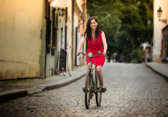 Beautiful brunette girl on a vintage bike