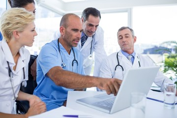 Doctor showing laptop pc to his colleagues