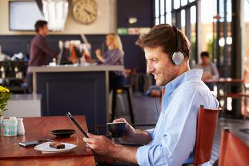 Man using digital tablet in a coffee shop