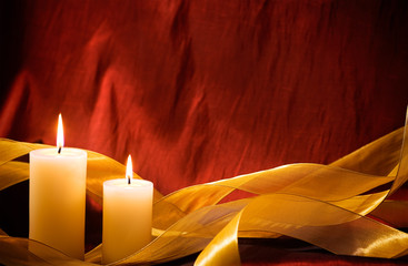 Christmas Candles and Gold Ribbon on luxurious red taffeta background with room for copy space.