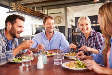 Fototapeta A group of friends eating at a restaurant obraz