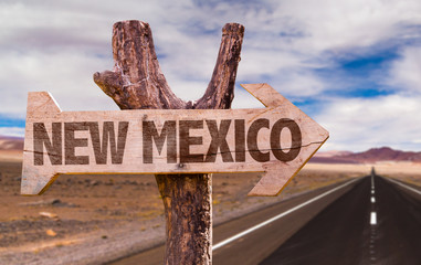 New Mexico wooden sign with desert road background