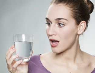 stunned young beautiful woman wearing purple shirt holding glass of pure tap water