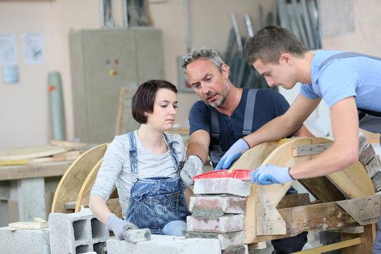 Instructor teaching teenagers brick laying