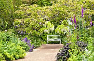 Pathway to white bench in English summer cottage garden