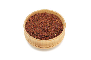 red pepper powder in a wooden bowl on a white background