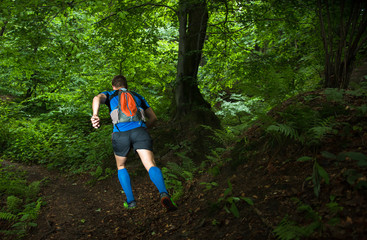 man with backpack running up the hill in the dark forest in the evening